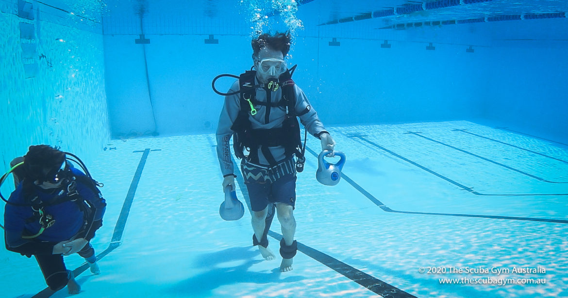 Two people underwater wearing scuba gear. The person in the centre focus is carrying kettle bells.