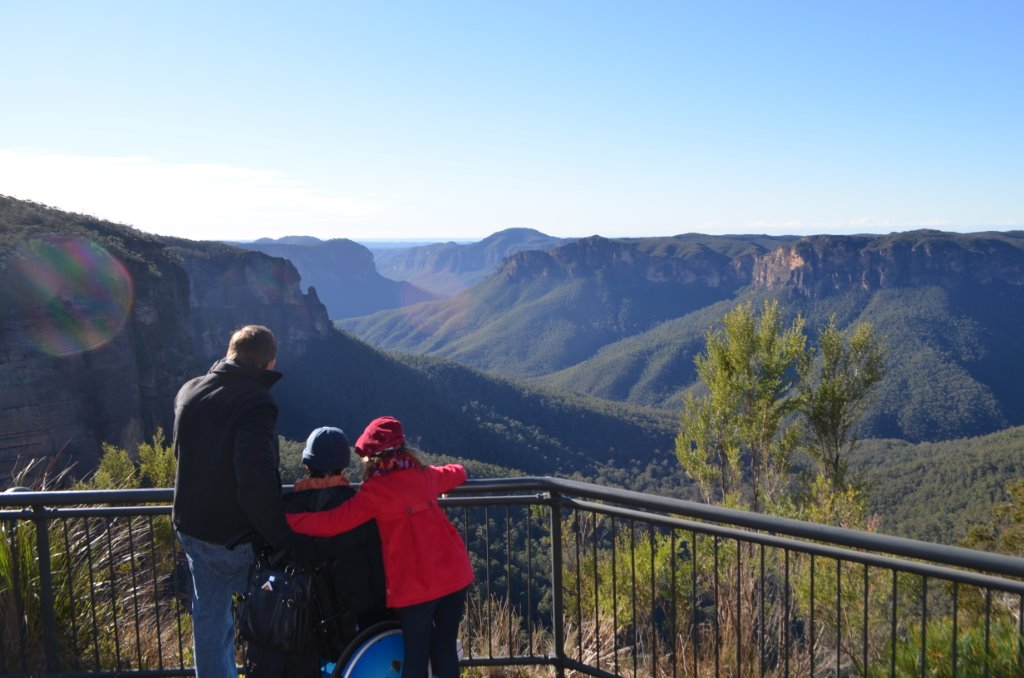 A family (adult, young person in wheelchair, young person standing) looking away from camera from a observation deck of the Blue Mountains - Accessible National Parks