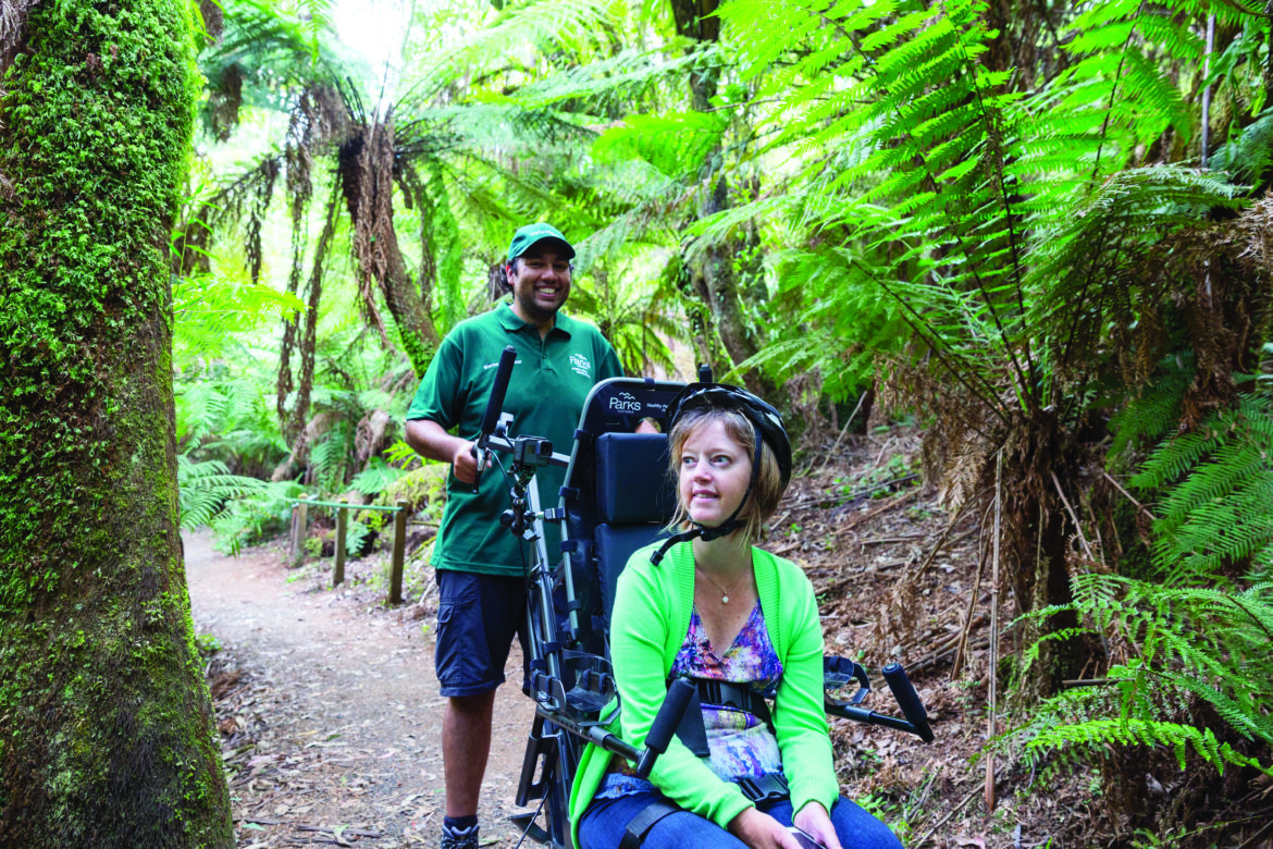 A woman wearing a helmet sitting in a TrailRider, with a sherpa behind her, escorting her along a rainforest track
