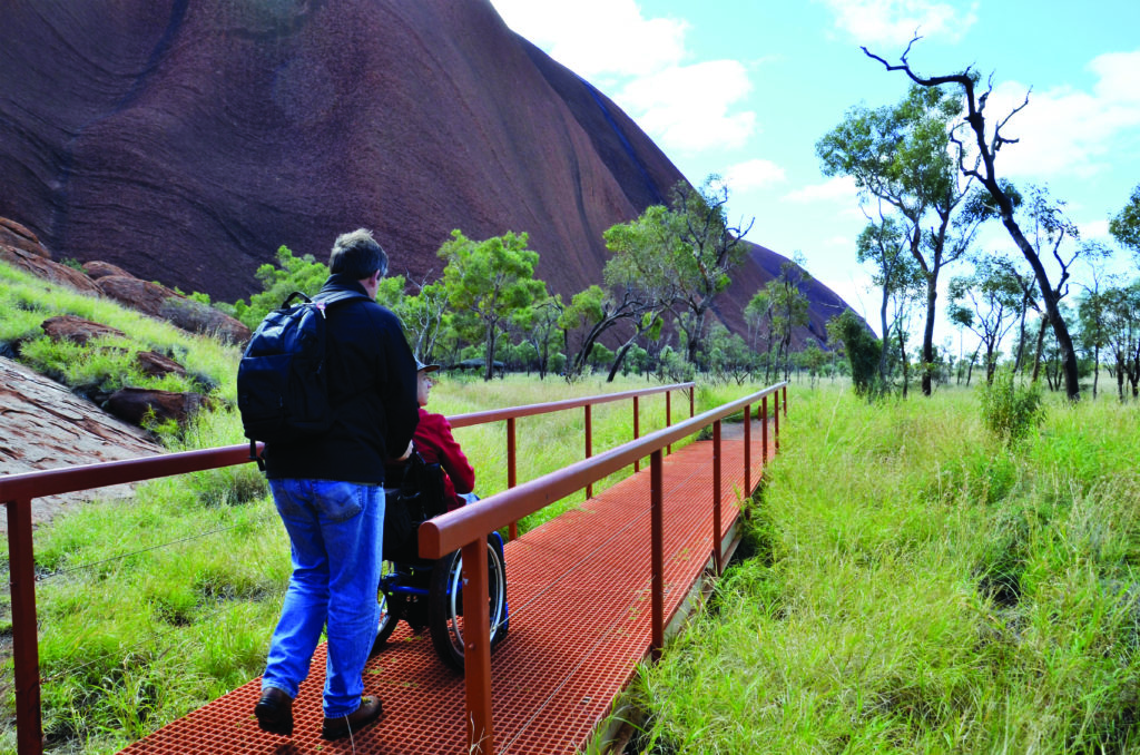 A man assisting a person in a wheelchair, walking away from the camera towards the base of Uluru - Accessible National Parks