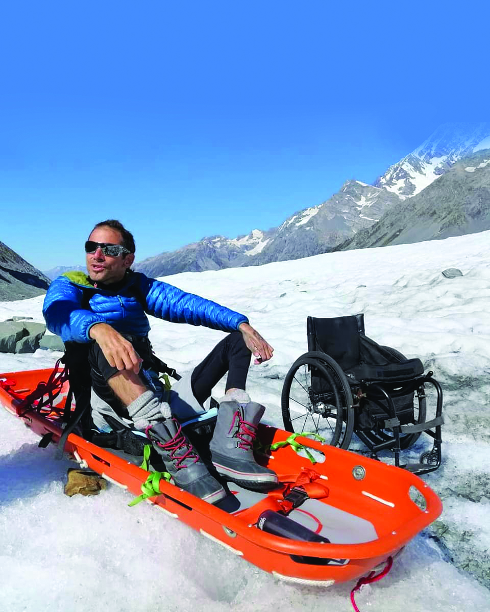 A man sitting on a sled, on snowy ground, with a wheelchair and a glacier in the background