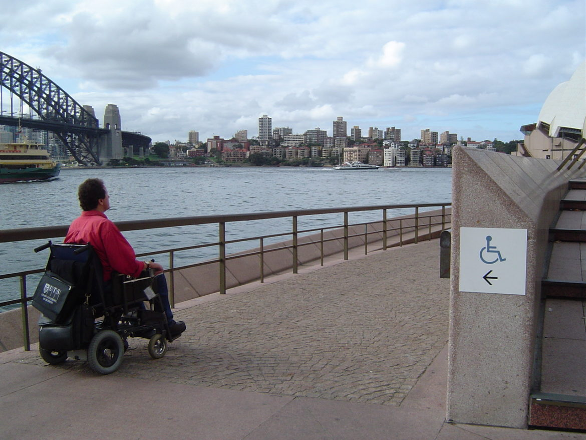 A man in a power wheelchair in front of Sydney Harbour. The Sydney Harbour Bridge is visible on the left, and a sign indicating wheelchair accessibility is on the right.