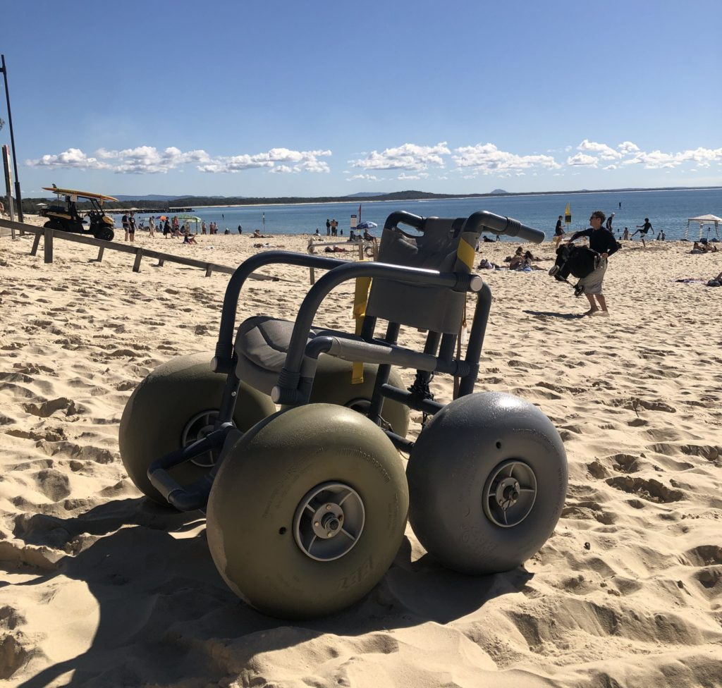 A beach wheelchair on sand, with beach-goers and water in the background