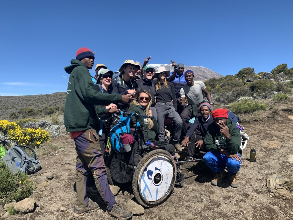 A group of twelve people standing in scrubland, one woman at the front of the group is sitting in a paratrekker chair. A mountain peak is visible in the background.