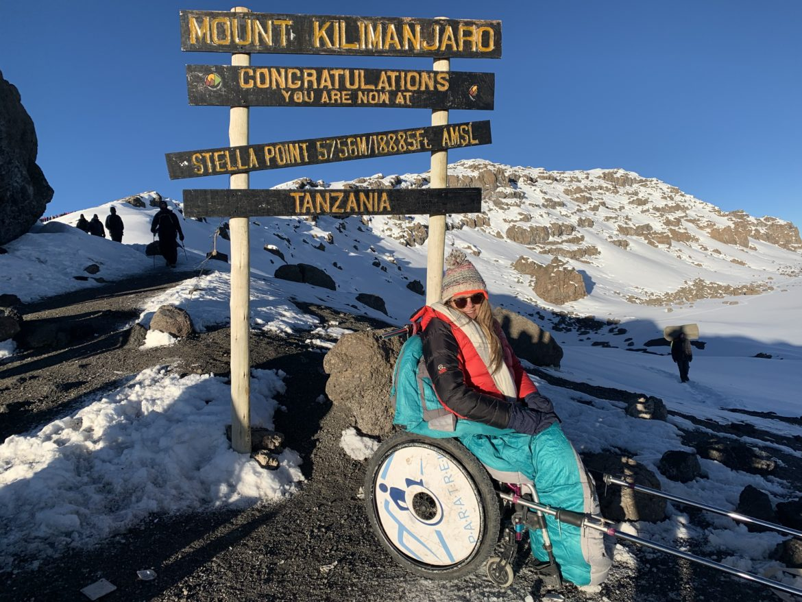 A woman sitting in a Paratrekker chair, in front of a sign that says congratulations for reaching Stella Point, Mount Kilimanjaro. Snowy mountain caps are visible in the background.