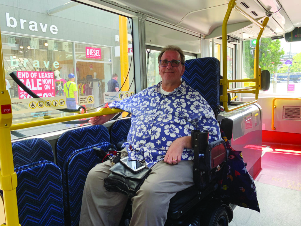 A man in a blue Hawaiian-print shirt, sitting in a wheelchair on a bus in the accessible seating section.