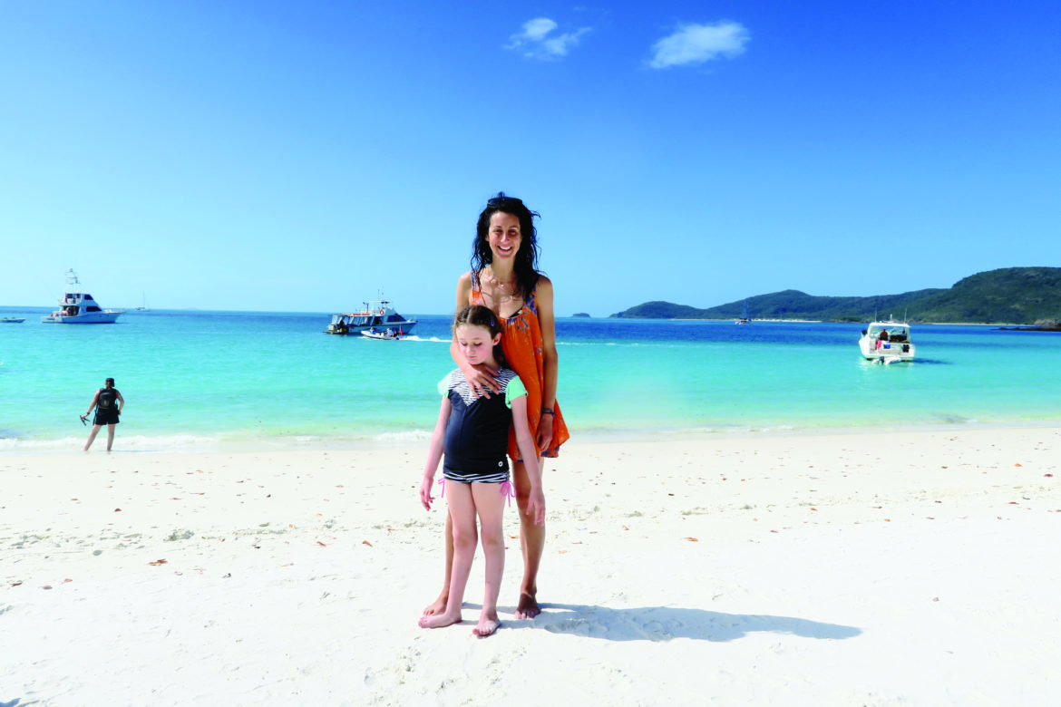 A woman and a child standing together on a white sand beach. There is another person in the distant background, and three boats on the water.