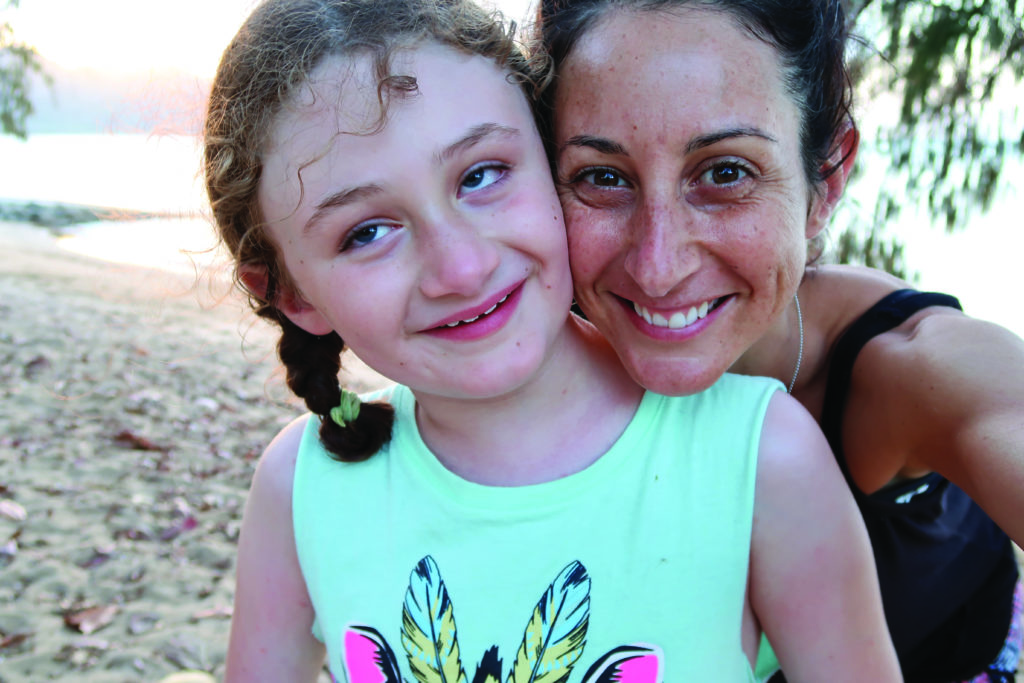 A selfie of a woman (right) and young girl (left), both wearing singlets and smiling, with a beach in the background.