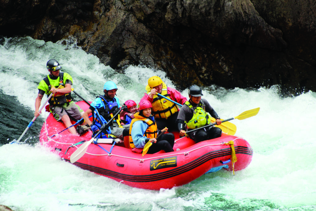 Six people in a white water raft with paddles, coming down rapids