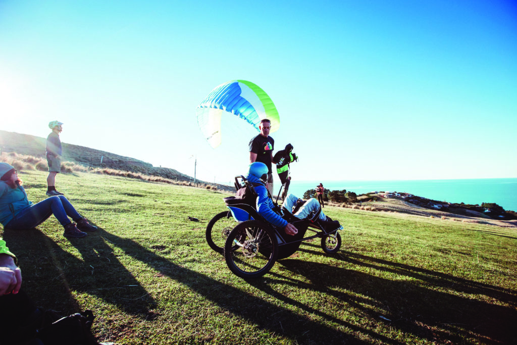 A person in a jacket and helmet sits in a wheeled paragliding chair, with people in the background watching and assisting. They are on a patch of grass overlooking water.