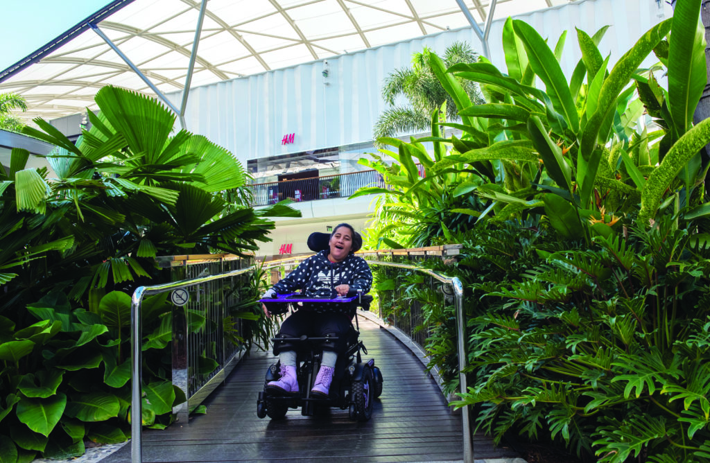A woman in a wheelchair comiing down a ramp, with foliage on either side.