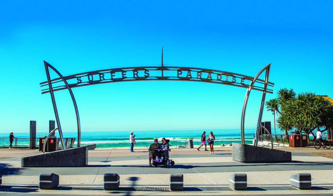 A distance shot of people underneath a sign that says Surfers Paradise, which stands out against bright blue sky in the background.