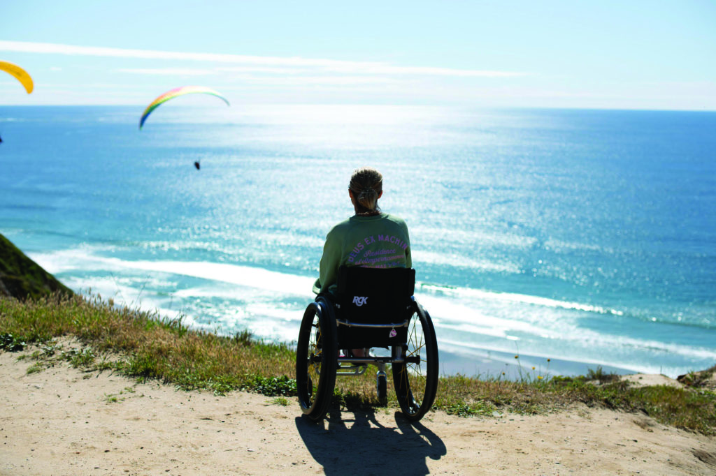 A woman in a wheelchair facing away from the camera, looking out over blue ocean water, and two paragliders in the air.