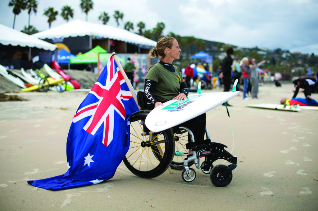 A woman in a wheelchair on the beach, with a surfboard across her lap. An Australian flag hangs from the  back of her wheelchair.