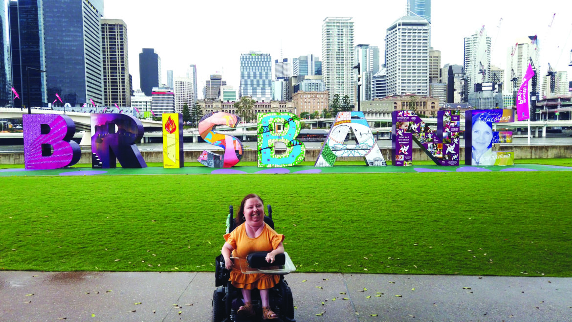 A woman in a wheelchair, in front of a multi-coloured sign that says BRISBANE, with a cityscape visible in the background