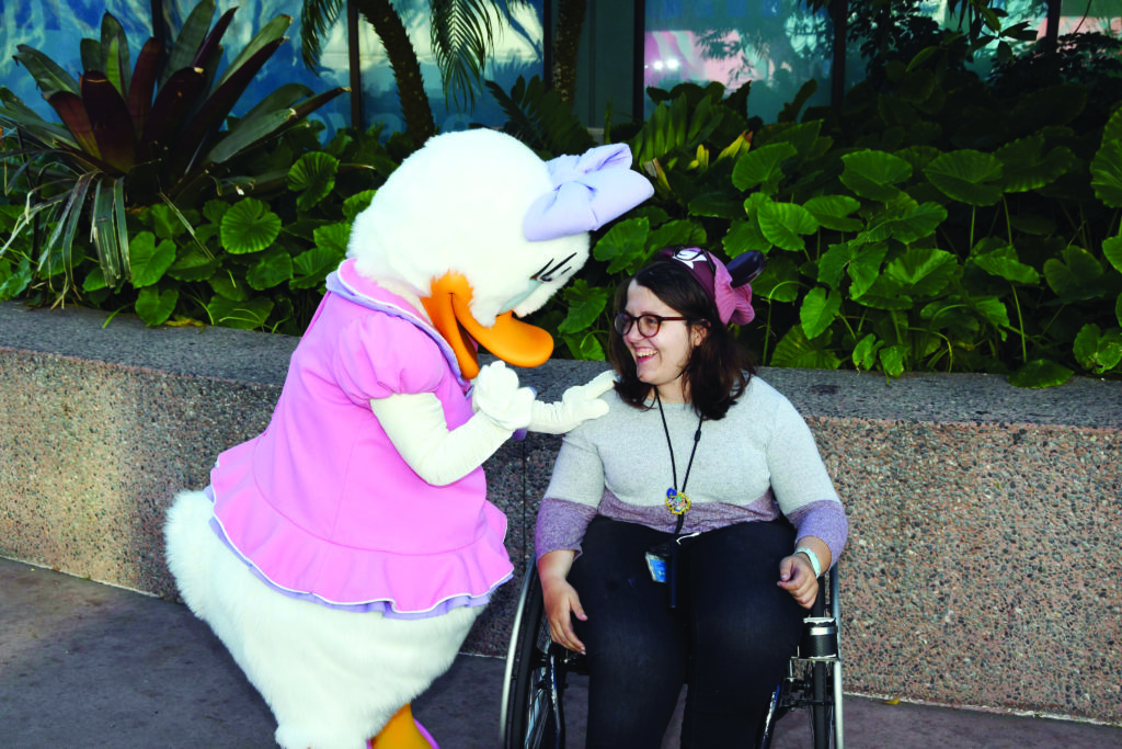 A young woman in a wheelchair, looking at (and smiling with) a Walt Disney World cast member in a duck costume.