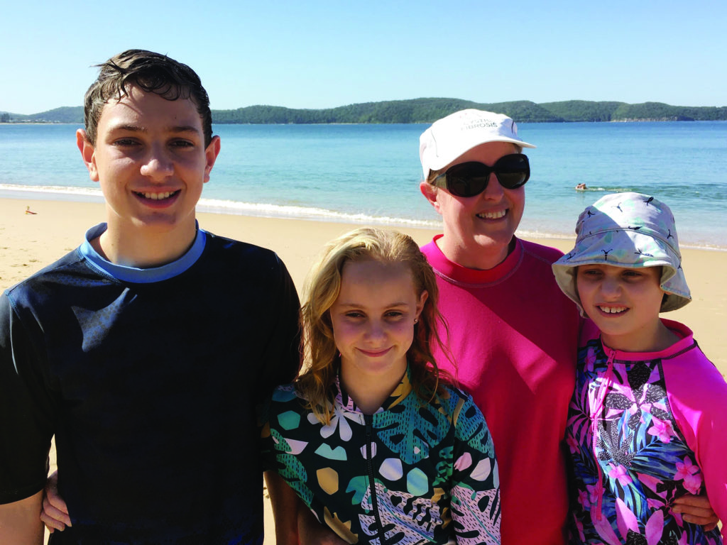 A portrait of a family of four in beach-wear, standing with a beach and horizon visible in the background