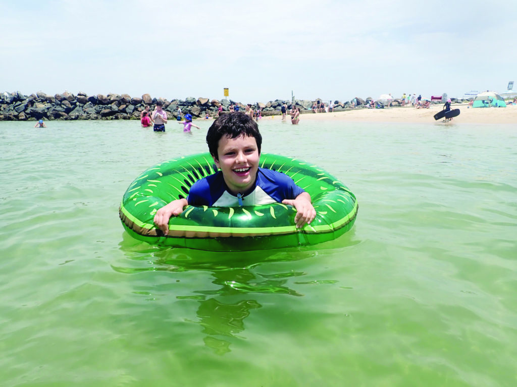 A child in a green inflatable donut, floating in water, with other beach-goers in the background along a rock wall and sand beach.