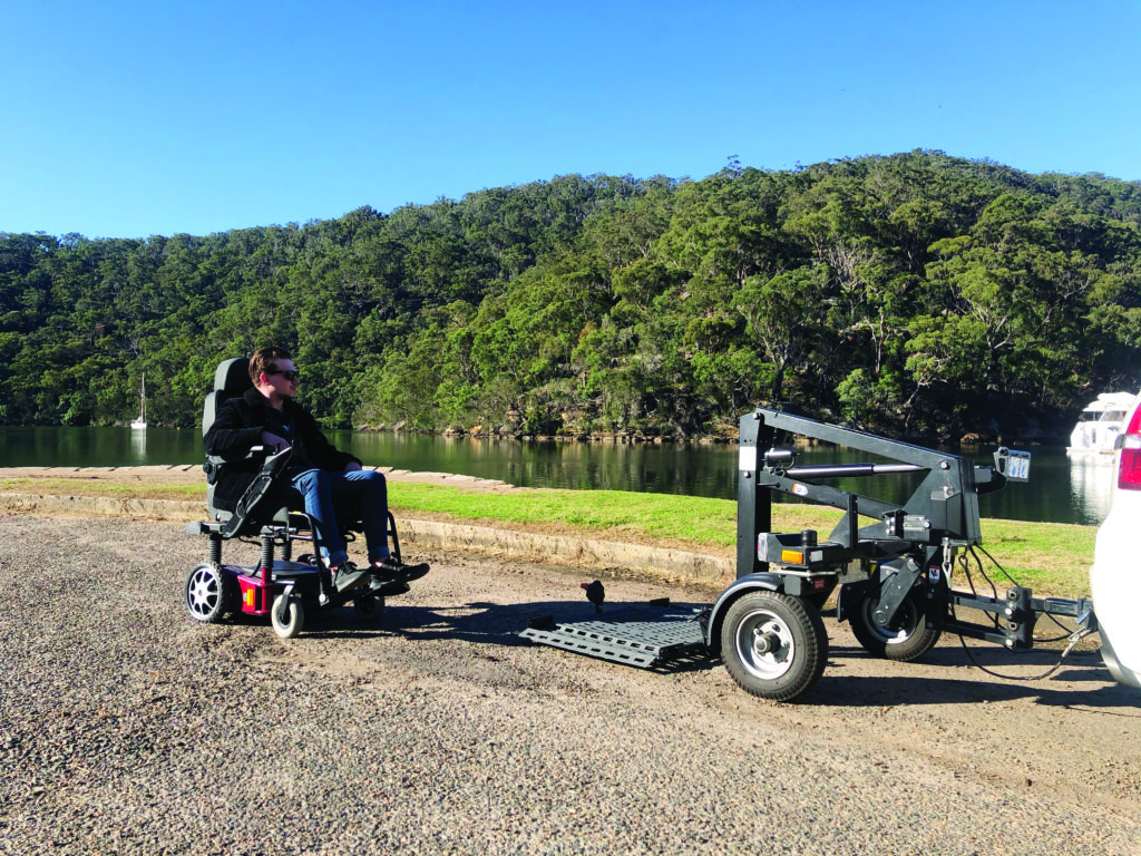 A person in a wheelchair, next to a Bruno Chariot Mobility Trailer, on a rough gravel road with a luscious green background.