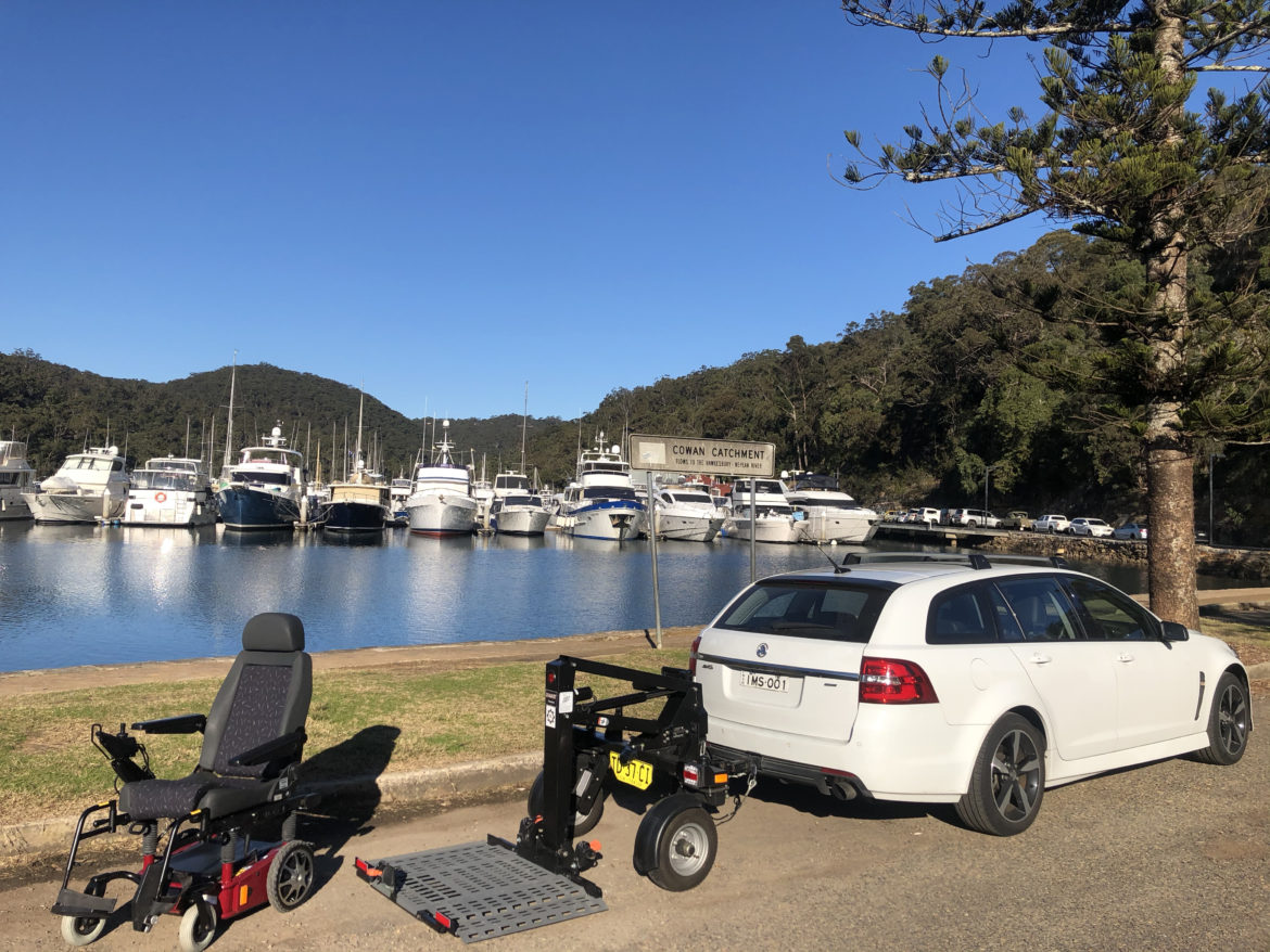 The Bruno Chariot Mobility Trailer behind a white car, with a wheelchair ready to load nextto it, and a bay with boats in the background.