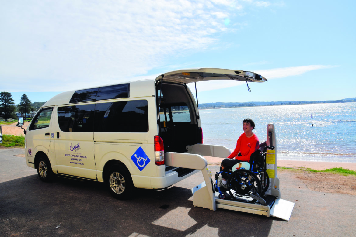 A young man in a wheelchair, sitting on a chair lift to be lifted into a white Integrity Car Sales and Rentals van. A beach and blue water is visible in the background.