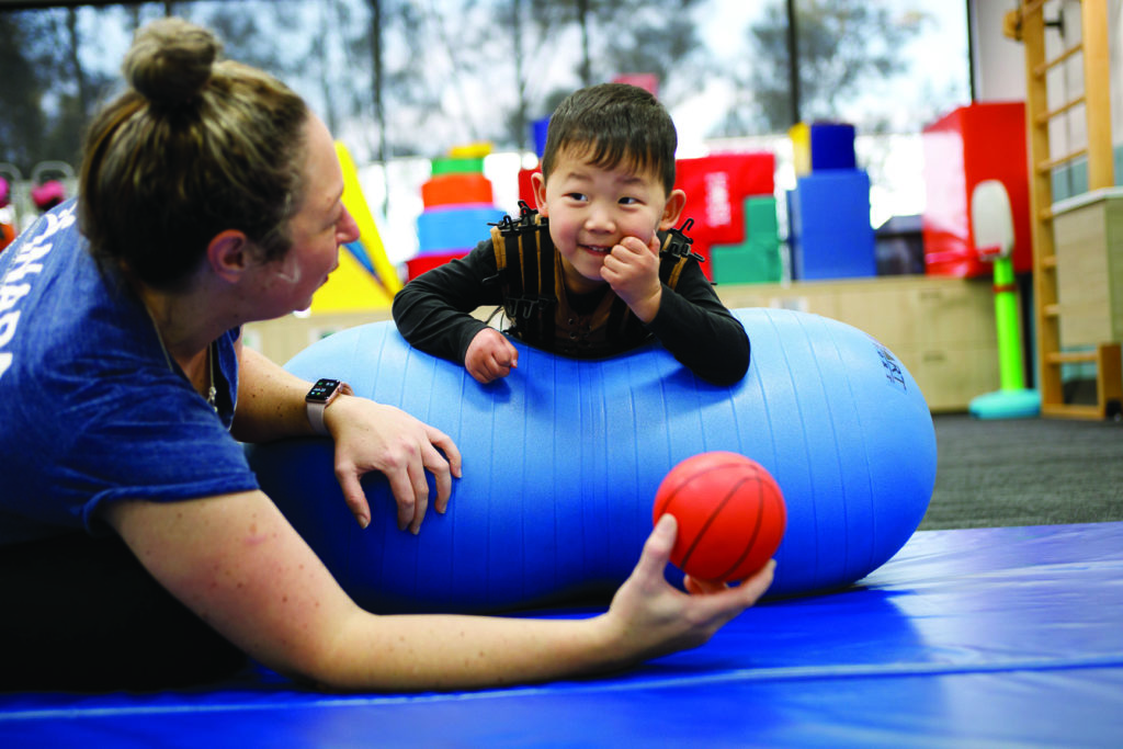 A child at the NAPA Centre laying across a blue therapy pillow, smiling at the person laying next to him, who is holding a small basketball.