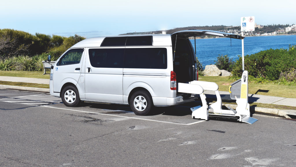 A silver Integrity Car Sales and Rentals van in a beach carpark, with some greenery visible in the background. The back hatch is open, and the chair lift lowered.