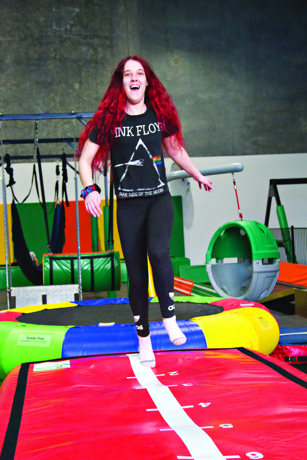 A young person with long red hair wearing a black t-shirt and long tights, jumping on a red air mattress in a Shine Shed Play Centre
