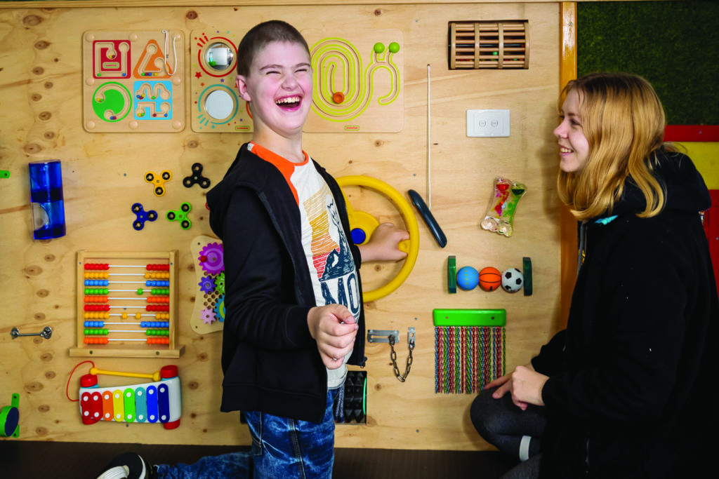 A young man and woman smiling, facing each other, standing in front of a sensory play wall.