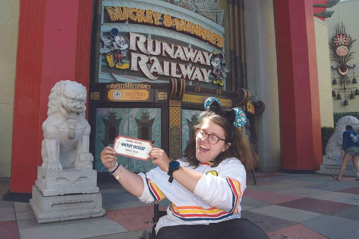 A young woman in a wheelchair holding out a ticket, wearing Mickey Mouse ears. In the background is the entrance to Mickey and Minnie's Runaway Railway.